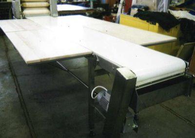Nerezový pásový dopravník se sklopnými bočními stoly za stojanem na výrobu rohlíků