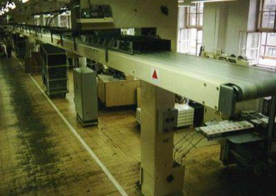 Sběrný pásový dopravník nad uličkou výrobní haly s elevátory od jednotlivých balících strojů